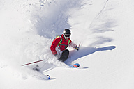 Austria, Zuers, Young man doing telemark skiing on Arlberg mountain - MIRF000337