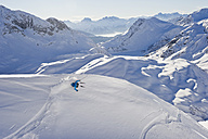 Austria, Zuers, Young man doing telemark skiing on Arlberg mountain - MIRF000349