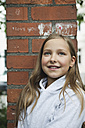 Germany, Berlin, Girl sitting in front of red brick wall - WESTF017474