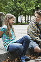 Germany, Berlin, Boy and girl sitting on curbstone - WESTF017492