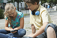 Germany, Berlin, Boy and girl sitting with cell phone and headphone - WESTF017513