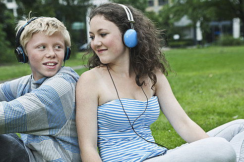 Germany, Berlin, Teenage couple with headphones listening music in park - WESTF017540
