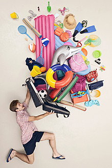 Germany, Artificial scene with man opening baggage full of beach toys - BAEF000319