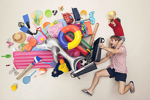 Germany, Artificial scene with man opening baggage full of beach toys - BAEF000322