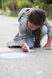 Germany, Bavaria, Huglfing, Girl drawing on street with chalk - RIMF000024