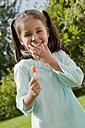 Germany, Bavaria, Huglfing, Girl holding lollipop in garden, smiling, portrait - RIMF000004