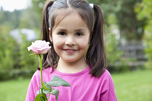 Germany, Bavaria, Huglfing, Girl holding flower in garden, smiling, portrait - RIMF000005