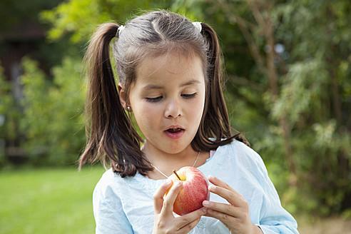 Germany, Bavaria, Huglfing, Girl looking at apple, close up - RIMF000006