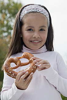 Germany, Bavaria, Huglfing, Girl holding pretzel in garden, smiling, portrait - RIMF000036