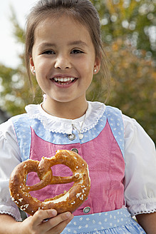 Germany, Bavaria, Huglfing, Girl holding pretzel in garden, smiling, portrait - RIMF000040