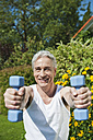 Germany, Bavaria, Mature man doing exercise with dumbbells - WESTF017625
