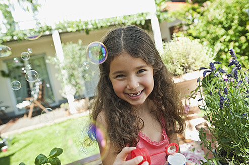 Germany, Bavaria, Girl blowing soap bubbles in garden, smiling, portrait - WESTF017700
