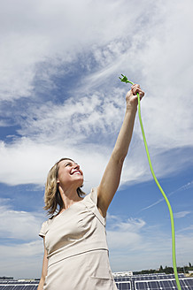 Germany, Munich, Woman holding electric cord in solar energy, smiling - WESTF017835