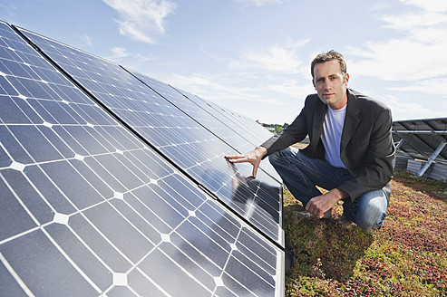 Germany, Munich, Man touching solar panel in solar plant, smiling, portrait - WESTF017850