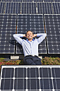 Germany, Munich, Mature man resting on panel in solar plant, smiling - WESTF017871