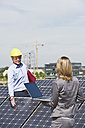 Germany, Munich, Engineers with laptop and discussing in solar plant - WESTF017889