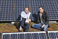 Germany, Munich, Two man sitting and relaxing in solar plant - WESTF017898