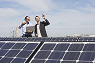 Germany, Munich, Engineer and man discussing in solar plant - WESTF017901