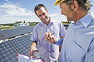 Germany, Munich, Man discussing with engineer in solar plant - WESTF017904