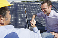 Germany, Munich, Man shaking hands with engineer in solar plant, smiling - WESTF017907
