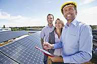 Germany, Munich, Engineer with man and woman in solar plant, smiling - WESTF017910