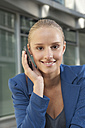 Germany, Bavaria, Teenage girl with cell phone, smiling, portrait - RNF000683