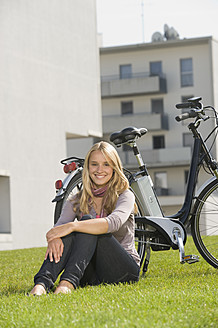 Germany, Bavaria, Teenage girl sitting in grass by bicycle, smiling, portrait - RNF000692