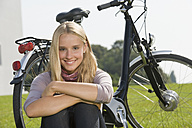 Germany, Bavaria, Teenage girl sitting in grass by bicycle, smiling, portrait - RNF000695