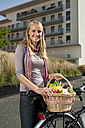 Germany, Bavaria, Teenage girl standing by bicycle holding basket, smiling, portrait - RNF000701