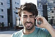 Germany, Cologne, Young man using cell phone, smiling, portrait - WESTF017976