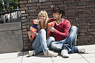 Germany, Cologne, Young couple eating french fries, smiling - WESTF018024