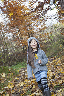 Germany, Huglfing, Girl holding leaf, smiling, portrait - RIMF000074