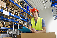 Germany, Bavaria, Munich, Manual worker with clipboard in warehouse, smiling - WESTF018034