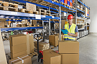 Germany, Bavaria, Munich, Manual worker with clipboard in warehouse, portrait - WESTF018037