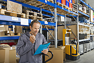 Germany, Bavaria, Munich, Manual worker checking list in warehouse - WESTF018058