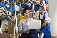 Germany, Bavaria, Munich, Manual workers using laptop in warehouse - WESTF018073