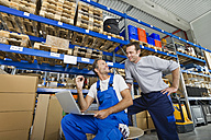 Germany, Bavaria, Munich, Manual workers using laptop in warehouse - WESTF018076