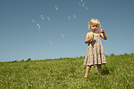 Germany, Bavaria, Girl blowing soap bubbles - RNF000735
