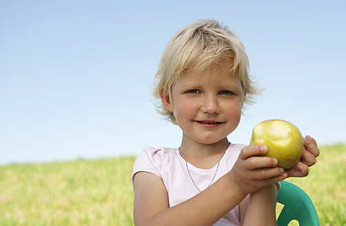 Germany, Bavaria, Girl with apple in grass, smiling, portrait - RNF000762