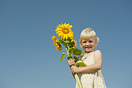 Germany, Bavaria, Girl with sunflower, smiling, portrait - RNF000742