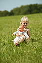 Germany, Bavaria, Girl with baby doll in grass meadow, smiling, portrait - RNF000745