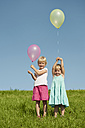 Germany, Bavaria, Girls standing in grass with balloons - RNF000754