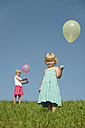 Germany, Bavaria, Girls standing in grass with balloons - RNF000757