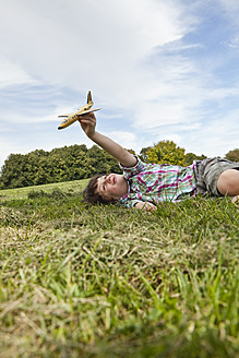 Germany, Bavaria, Boy playing with model airplane in park - SKF000548