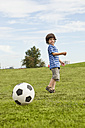 Germany, Bavaria, Boy playing with soccer ball in park - SKF000551