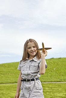 Germany, Bavaria, Girl playing with model airplane in park, smiling, portrait - SKF000557