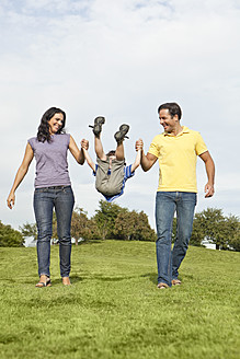 Germany, Bavaria, Parents playing with son in park, smiling - SKF000599