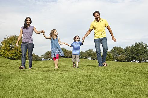 Germany, Bavaria, Family walking in grass at park - SKF000620