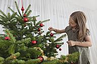 Germany, Munich, Girl decorating christmas tree - SKF000632