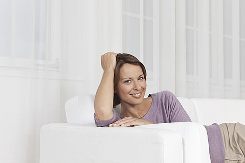 Germany, Munich, Woman sitting on couch, smiling, portrait - SKF000635
